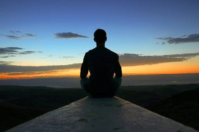 person-meditating-on-the-tip-of-wall