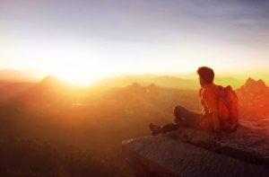 person-sittinig-on-edge-facing-sunset