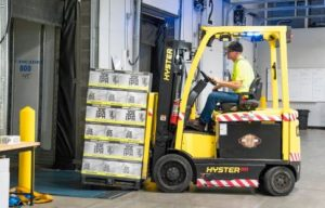 person-riding-a-yellow-forklift-with-boxes